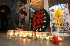 A man places a candle at a memorial inside the Moscom railway station in Saint Petersburg on January 25, 2011.