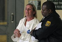 An officer escorts Julie Powers Schenecker to Orient Road Jail in Tampa, on Friday.