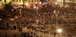 People defy a government curfew as they continue to occupy Tahrir Square in Cairo on Sunday.