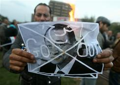 An Iraqi man burns a picture of Egyptian President Hosni Mubarak during a protest Sunday in Baghdad in support of Egyptian protesters demanding his ouster after 30 years in power.