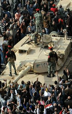 Egyptian soldiers address protesters Sunday as they gather around a tank at Tahrir Square in Cairo amid increasing lawlessness, a rising death toll and a spate of jail breaks.