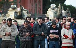 Protesters pray in sight of army tanks Monday in Tahrir Square in Cairo.