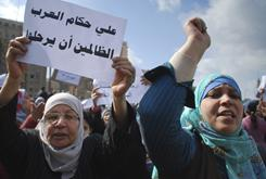 """Women, one holding a poster reading """"All Arab oppressors must leave,"""" react during an anti-government demonstration in Cairo on Monday."""
