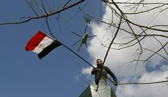 An Egyptian demonstrator holds up the national flag during Monday's protest in Tahrir Square in Cairo. It is the seventh day of an uprising against President Hosni Mubarak.