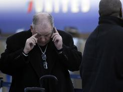 Jere White of Kansas City, Mo., books a hotel after his flight was canceled at O'Hare International Airport in Chicago on Tuesday.
