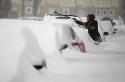A woman tries to clear her windshield Wednesday in Milwaukee. The area was under a blizzard warning and some freeways were shut down.