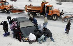 A group of people stop Wednesday along Interstate 91 to help push a car out of a snowbank during a storm in Windsor, Conn.