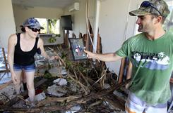 Nathan La Fauci, right, shows his partner Elisha Verrent a photo found in the rubble of their home at Tully Heads, Australia on Saturday after Cyclone Yasi brought heavy rain and howling winds gusting to 186 mph.