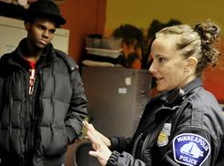 Zal Warsame, left, listens as Minneapolis police officer Jeanine Brudenell talks with Somali young people who were interested in signing up for a Minneapolis Police Department Citizens Academy geared toward Somali kids.