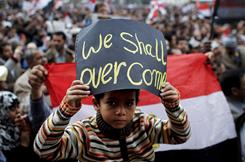 """An Egyptian boy holds a sign reading """"We Shall overcome"""" as anti-government protesters remain in Cairo's Tahrir Square on Sunday."""