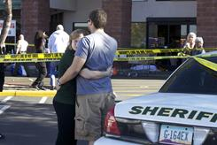 Bystanders embrace at the scene where Rep. Gabrielle Giffords and others were shot outside a Safeway grocery store in Tucson on Jan. 8.