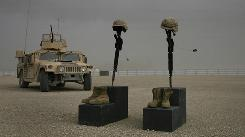 Boots, helmet, weapon and dog tags are displayed at Camp Bastion in Afghanistan to honor a Marine killed in April 2008.