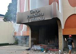 Smoke lingers at the Christian Pentecostal Church in Temanggung, Indonesia, after a Muslim mob set it on fire to demand the death penalty for a Christian man convicted of blaspheming against Islam.