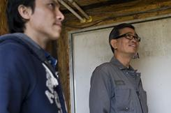 Vietnamese farmers, Hoangson Nguyen, 34, left, and Tuan Nguyen, 54, discuss the systems at one of Tuan's chicken houses. Tuan has been Hoangson's mentor for his farming venture.