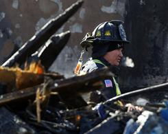 A firefighter inspects the aftermath of a fatal explosion in a residential neighborhood in Allentown, Pa., on Thursday.