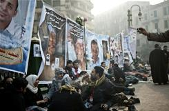 Anti-government demonstrators rest early Friday morning in front of posters of people killed during Egypt's political crisis as the 18th day of protests against President Hosni Mubarak's regime begins.
