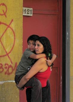 A woman holds a child as they stand outside a building as a precaution Friday after a magnitude-6.8 earthquake in Concepcion, Chile.