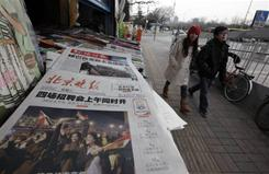 "A Chinese couple walks past a newspaper front page showing Egyptians celebrating and title ""Mubarak hands over power"" at a newsstand in Beijing, China on Saturday."