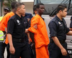 A Somali pirate is escorted by Malaysian police officers as he leaves Bukit Jalil Police Station in Kuala Lumpur, Malaysia, on Jan. 31.