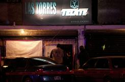 Mexican police stand guard at the Bar las Torres after a shooting that killed several people in Ciudad Juarez on Thursday.