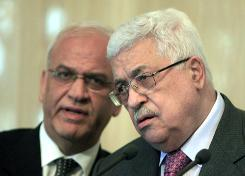 Senior Palestinian negotiator Saeb Erekat, left, speaks to Palestinian Authority President Mahmoud Abbas during a press conference in Cairo on Jan. 24.
