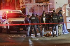 State police and forensic experts stand outside a nightclub Saturday after gunmen opened fire and hurled a grenade in Guadalajara, Mexico.