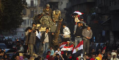 Egyptians climb atop of an army tank Sunday in Tahrir Square in Cairo.
