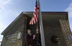 Postal employee Christine Storm retires the flag as she closes up the Iroquois, Ill., branch for the day Saturday.