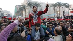 Remaining Egyptian protesters shout slogans as they are surrounded by army soldiers trying to lead them away from Tahrir Square in Cairo.