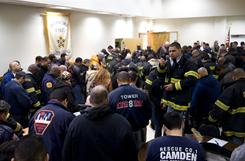 Camden firefighters and police officers bow their heads in prayer before marching in protest of the city's layoffs on Jan. 18.