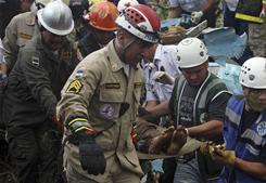 Rescue workers remove bodies Monday from a commercial airplane that crashed in Las Mesitas, Honduras. All 14 passengers were killed.