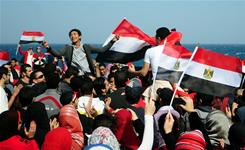 Egyptians celebrate the resignation of President Hosni Mubarak during a rally in Alexandria on Tuesday. Protest leaders will resume demonstrations if a transitional government isn't appointed soon.