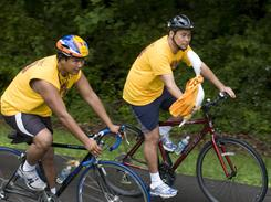 Jigme Norbu, left, and Kunga Norbu, nephews of the Dalai Lama, ride into the Tibetan Culture Center in Bloomington, Ind., in 2008 with the Tibetan Freedom Torch.