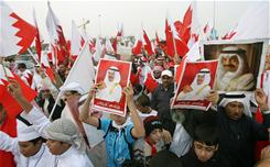 Pro-government demonstrators hold pictures of Prime Minister Sheikh Khalifa bin Salman al-Khalifa in Rifaa, Bahrain, as anti-government protests took place in the capital Manama, Feb. 16.