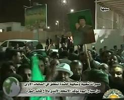 An image grab taken on Wednesday from footage broadcast by Libya's state television shows Libyans holding portraits of leader Moamer Kadhafi as they chant slogans during a demonstration in his support in the southern city of Sebha.
