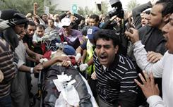 A Bahraini anti-government demonstrator lies injured on a stretcher in Manama, Bahrain early Thursday morning, after riot police with tear gas and clubs drove protesters from a main square.