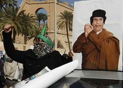 A supporter of Libyan leader Moammar Gadhafi shouts slogans next to his picture while taking part in a pro-government rally in Tripoli on Thursday.