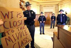 Wisconsin State Patrol officers are stationed Wednesday outside the office of Gov. Scott Walker as thousands of demonstrators occupy the State Capitol building, including a protester holding a sign.