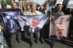 Pro-government Iranians carry photos of opposition leaders Mir Hossein Mousavi, left, and Mahdi Karroubi, right, during a rally Friday.