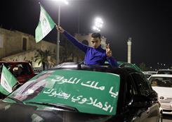A supporter of Libyan President Moammar Gadhafi holds a flag during a pro-government demonstration in Tripoli on Thursday.