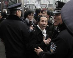 A man confronts police officers in front of a cinema that was a planned protest site in Shanghai on Sunday.
