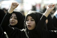 Bahraini women shout slogans early in Pearl Square in the capital Manama on Sunday. Police and troops withdrew frem the square Saturday in what appeared to be a conciliatory move.