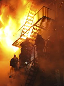 Firefighters stand on the fire escape as winds whip the flames from a five-alarm fire in the Brooklyn borough of New York late Saturday.