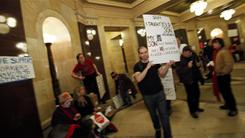Teacher Michael Mulvey and other demonstrators protest a plan to scrap most public workers' union rights at the State Capitol in Madison, Wis.