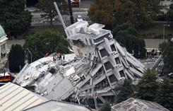 Rescue workers climb onto the collapsed Pyne Gould Guinness Building in central Christchurch, New Zealand, Tuesday. A powerful earthquake killed at least 76 people and trapped dozens more.