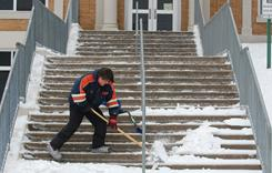 Juan Ramos cleans steps Monday, which is a school holiday, at Fremont Elementary School in Battle Creek, Mich.