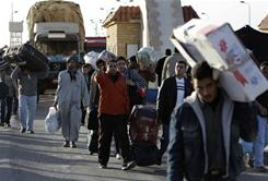 Egyptians who fled from Libya carry their belongings at the Egyptian-Libyan border in Salloum, Egypt, on Tuesday.
