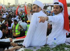 Habib Maqdad, foreground second right, a Bahraini Shiite Muslim cleric who was standing trial for plotting against the regime, and another unidentified former political prisoner wave to well-wishers during a parade Wednesday.