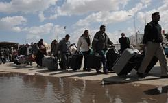 People flee Libya Thursday at the border near the village of Ras Ajdir, Tunisia.