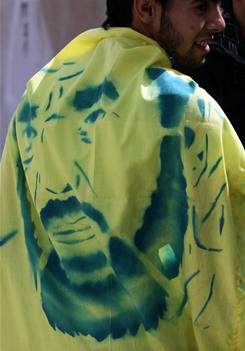 A Bahraini man wears a banner with the image of Hassan Meshaima, a prominent self-exiled Shiite opposition leader.